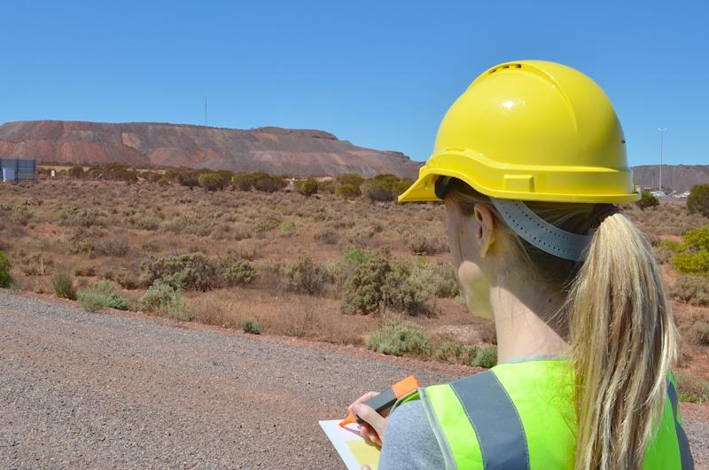 A woman in a hard hat with a notebook overlooking a potential mine site.