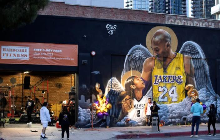 People stop by a mural of late Kobe Bryant, who perished one year ago alongside his daughter and seven others when their helicopter crashed into a hillside, in Los Angeles
