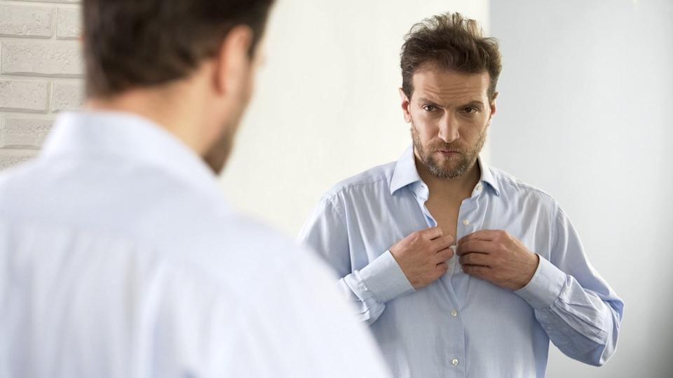 Sleepy man wearing shirt, preparing for work in morning, unhappy with appearance