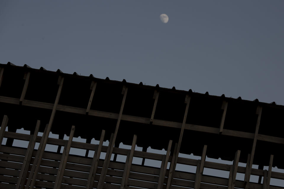 The moon rises over the Mughrabi Bridge, a wooden pedestrian bridge connecting the wall to the Al Aqsa Mosque compound, in Jerusalem's Old City, Tuesday, July 20, 2021. The rickety bridge allowing access to Jerusalem's most sensitive holy site is at risk of collapse, according to experts. But the flashpoint shrine's delicate position at ground-zero of the Israeli-Palestinian conflict has prevented its repair for more than a decade. (AP Photo/Maya Alleruzzo)
