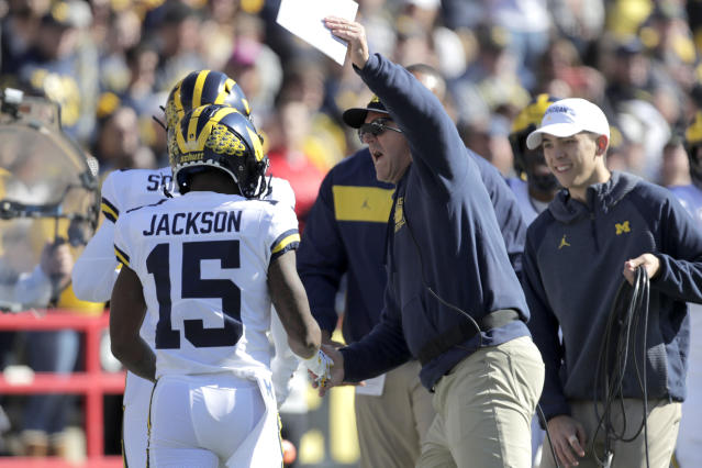 Michigan head coach Jim Harbaugh, center, congratulates Giles Jackson after he returned the opening kickoff from Maryland for a touchdown during the first half of an NCAA college football game, Saturday, Nov. 2, 2019, in College Park, Md. (AP Photo/Julio Cortez)