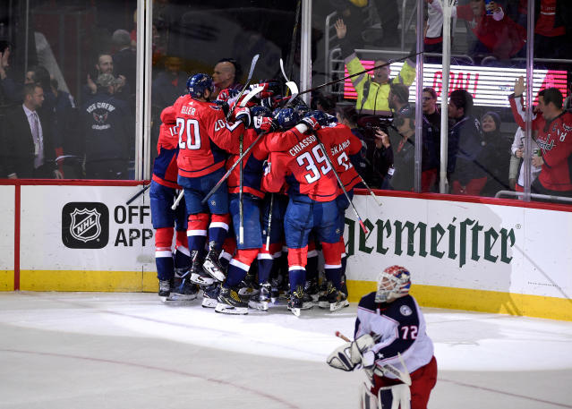 Washington Capitals celebrate after Game 5 of an NHL first-round hockey playoff series as Columbus Blue Jackets goaltender Sergei Bobrovsky (72), of Russia, skates by, Saturday, April 21, 2018, in Washington. The Capitals won 4-3 in overtime. (AP Photo/Nick Wass)