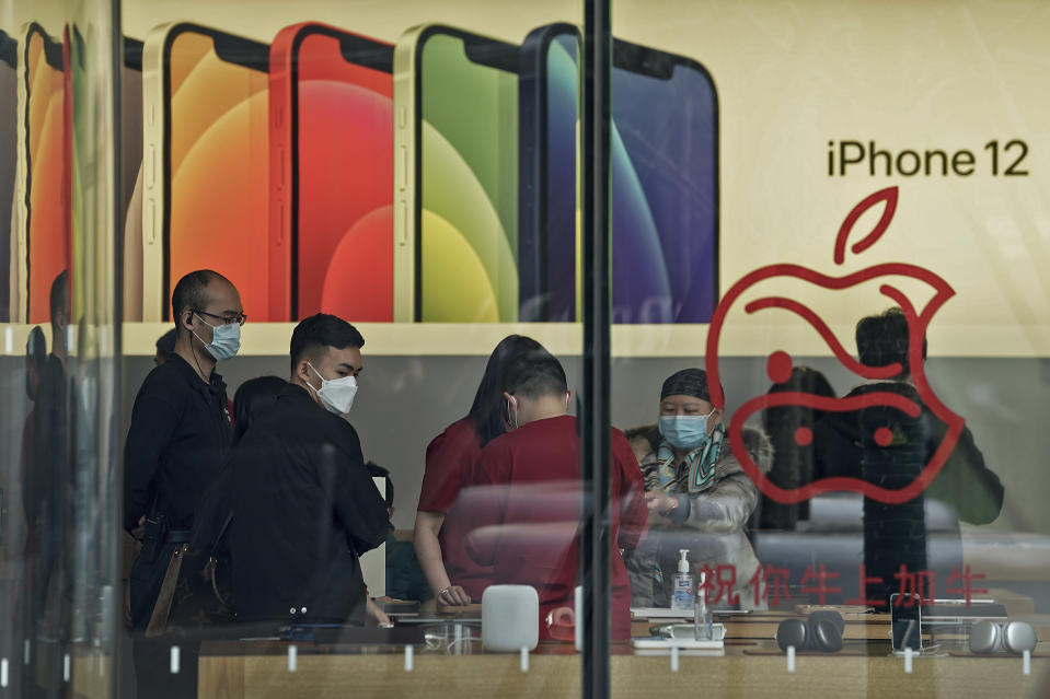 """People wearing face masks to help curb the spread of the coronavirus look at iPad devices at an Apple store at the capital city's popular shopping mall in Beijing on Wednesday, Feb. 24, 2021. China's commerce minister appealed to Washington for """"join efforts"""" revive trade but gave no indication Wednesday when tariff war talks might resume or whether Beijing might offer concessions. (AP Photo/Andy Wong)"""