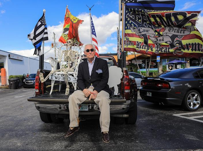 Conservative political consultant and lobbyist Roger Stone sits beside a skeleton in the bed of Boca Raton residents Robert and Lisa Beche's pickup truck parked on Southern Blvd. after President Trump took his last motorcade ride from Palm Beach International Airport to Mar-a-Lago, January 20, 2021.