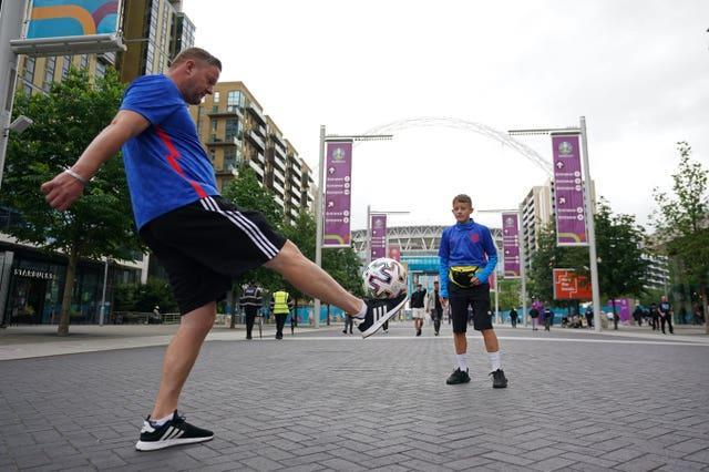 Fans play football outside Wembley Stadium several hours before the semi-final match with Denmark