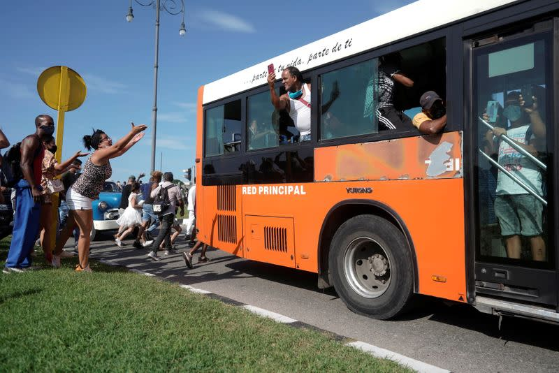 People ask passengers of a bus to join them during a during a protest against and in support of the government, in Havana