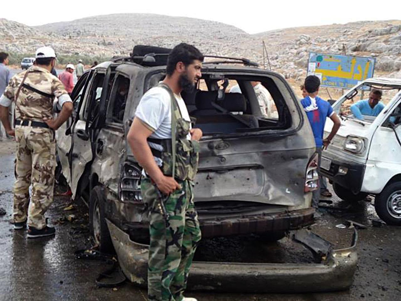 This citizen journalism image provided by Edlib News Network, ENN, which has been authenticated based on its contents and other AP reporting, shows Syrian rebels with damaged cars at the scene where a car bomb exploded at a crossing point along Syria's volatile border with Turkey, in Bab al-Hawa, Syria, Tuesday, Sept. 17, 2013. (AP Photo/Edlib News Network ENN)