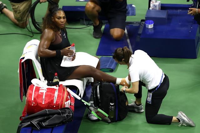 Serena Williams gets her right ankle taped early in the first set against her sister, Venus, on Friday night at Arthur Ashe Stadium. (Getty Images)