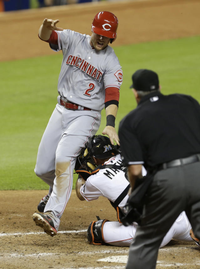 Cincinnati Reds' Zack Cozart (2) scores the game tying run on a sacrifice fly by Todd Frazier against the Miami Marlins in the eighth inning of a baseball game in Miami, Thursday, July 31, 2014. (AP Photo/Alan Diaz)