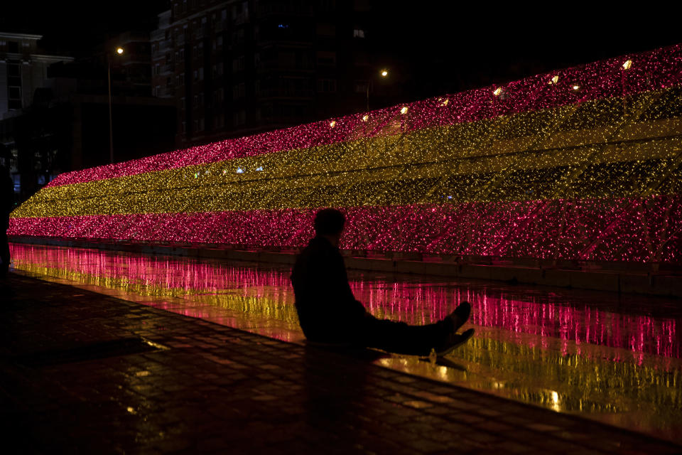 A man sits in front of a bank of Christmas lights in the colors of the Spanish flag in Madrid, Spain, Friday, Nov. 27, 2020. People are waiting to see what restrictions will be in place over Christmas and the New Year as Spanish regions are continuing to adjust their various limitations against the coronavirus pandemic. (AP Photo/Paul White)