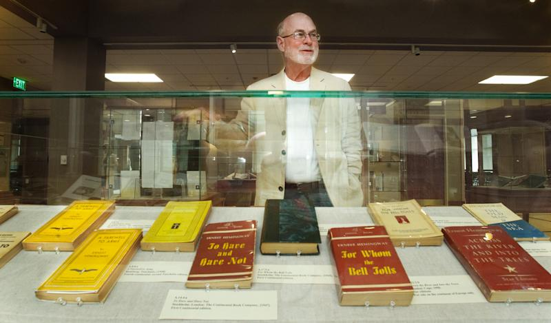 Dr. Edgar Grissom of Mississippi stands behind Ernest Hemingway books published in London, Stockholm and Hamburg, at the University of South Carolina in Columbia, S.C. Tuesday Sept. 25, 2012.  Grissom has donated his  Hemingway collection of 1,200 novels and first editions as well as 2,500 additional items that include editor's proofs to the university. (AP Photo/The State,Tim Dominick ) ALL LOCAL MEDIA OUT, (TV, ONLINE, PRINT)