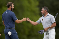 Dustin Johnson, left, bumps fists with Lee Westwood, of England, on the 18th green during the second round of the Masters golf tournament on Friday, April 9, 2021, in Augusta, Ga. (AP Photo/David J. Phillip)