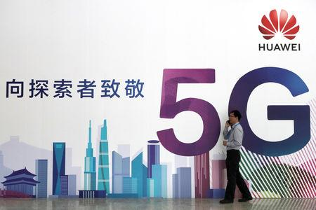 Man talks on his phone beside a Huawei's billboard featuring 5G technology at the PT Expo in Beijing