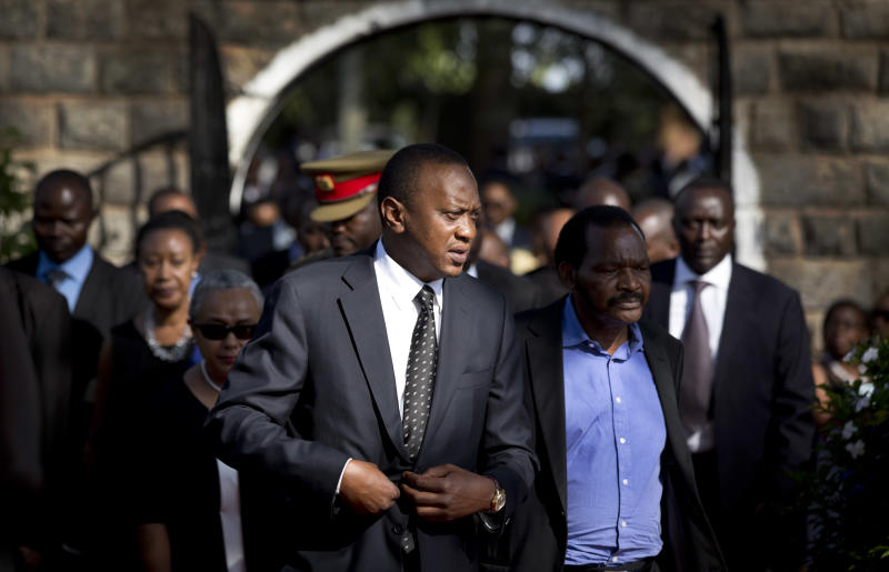 Kenya's President Uhuru Kenyatta, center-left, arrives for the burial ceremony of his nephew Mbugua Mwangi and Mwangi's fiancee Rosemary Wahito, who were both killed in the Westgate Mall terrorist attack, at the burial site in the village of Ichawara, Kenya Friday, Sept. 27, 2013. Investigators have recovered a vehicle believed to have been used by the terrorists who led the attack at a Nairobi mall that killed at least 67 people, a top Kenyan government official said Friday. (AP Photo/Ben Curtis)