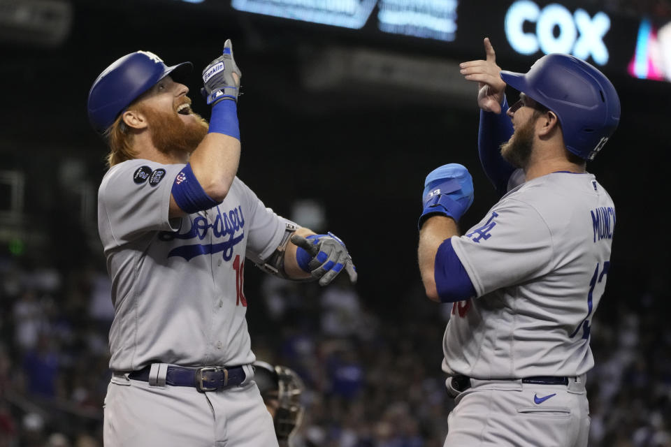 Los Angeles Dodgers' Justin Turner, left, celebrates with Max Muncy after hitting a two-run home run against the Arizona Diamondbacks during the seventh inning of a baseball game Saturday, July 31, 2021, in Phoenix. (AP Photo/Rick Scuteri)