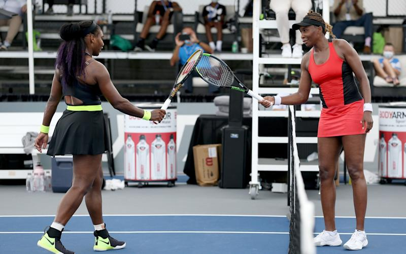 Serena Williams (L) and Venus Williams touch rackets - Getty Images