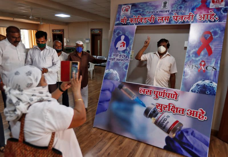 Man poses behind a cardboard cut-out after receiving a dose of COVISHIELD vaccine in Satara district
