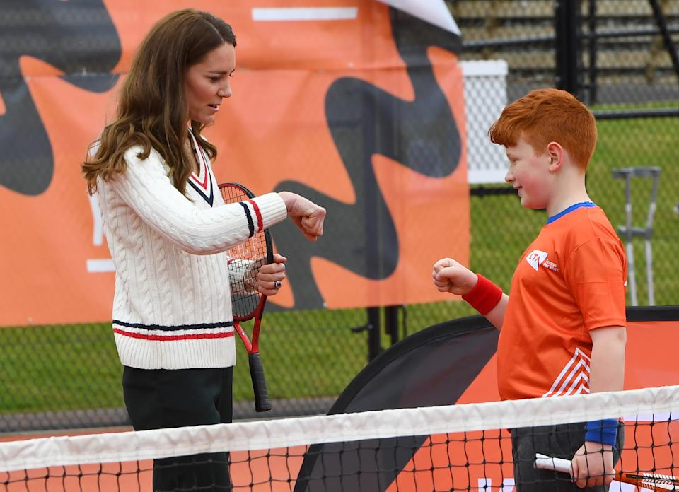 EDINBURGH, SCOTLAND - MAY 27: Catherine, Duchess of Cambridge fist bumps a schoolchild during a tennis game as they take part in the Lawn Tennis Association's (LTA) Youth programme, at Craiglockhart Tennis Centre on May 26, 2021 in Edinburgh, Scotland. (Photo by Andy Buchanan - WPA Pool/Getty Images)