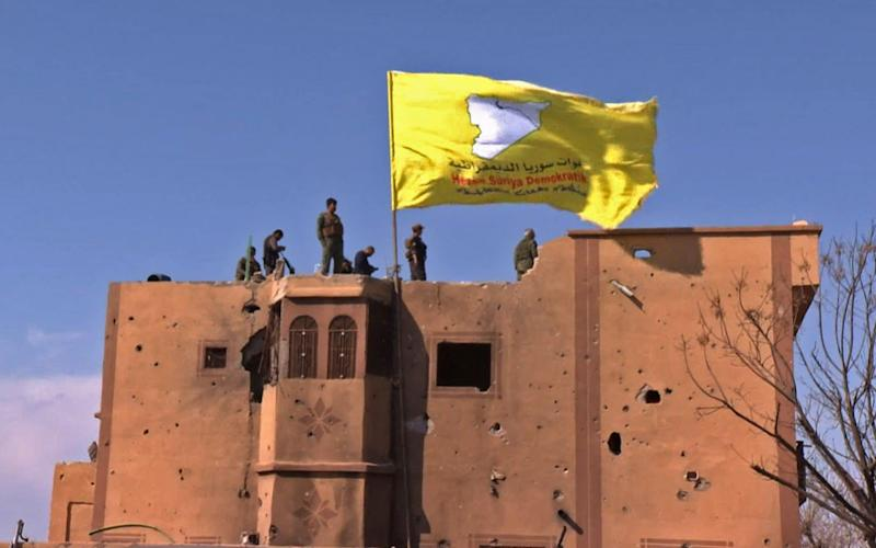 Syrian Democratic Forces raising their flag atop a building in the Islamic State group's last bastion in the eastern Syrian village of Baghuz after defeating the jihadist group. March 23, 2019. - AFP