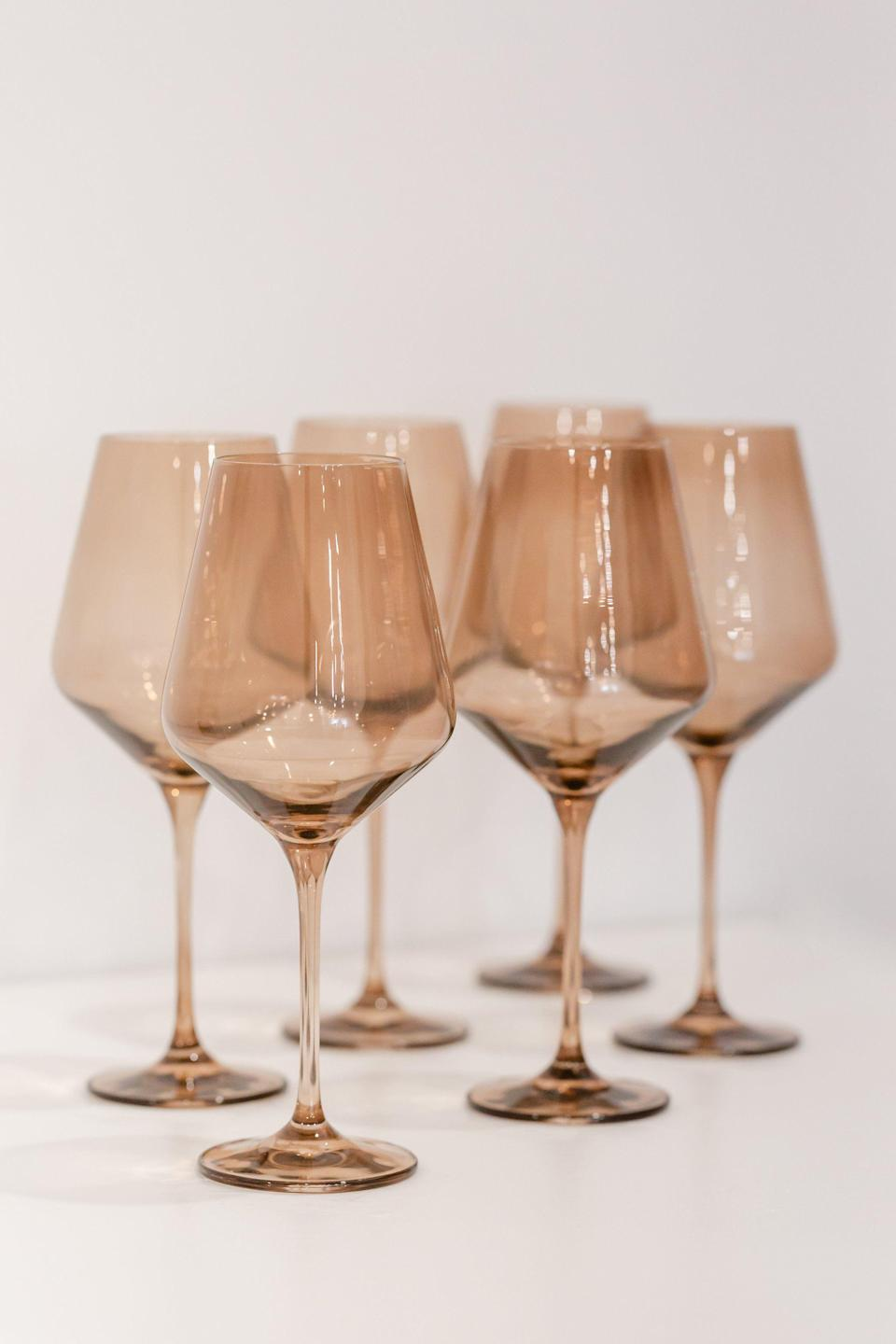 """<p><strong>Estelle Colored Glass</strong></p><p>estellecoloredglass.com</p><p><strong>$175.00</strong></p><p><a href=""""https://www.estellecoloredglass.com/collections/glassware/products/estelle-colored-wine-stemware-smoke"""" rel=""""nofollow noopener"""" target=""""_blank"""" data-ylk=""""slk:Shop Now"""" class=""""link rapid-noclick-resp"""">Shop Now</a></p><p>Estelle's colored-glass stemware, available in a set of six, is a great gift for the friend who loves to host. </p>"""