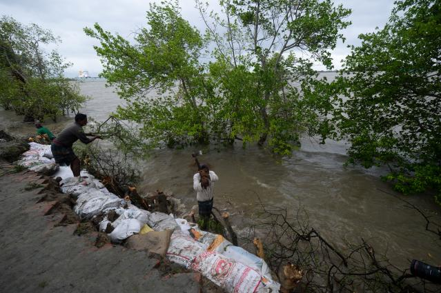 """Villagers reinforce an embankment with sacks of soil ahead of the expected landfall of cyclone Amphan, in Dacope on May 20, 2020. - Several million people were taking shelter and praying for the best on Wednesday as the Bay of Bengal's fiercest cyclone in decades roared towards Bangladesh and eastern India, with forecasts of a potentially devastating and deadly storm surge. Authorities have scrambled to evacuate low lying areas in the path of Amphan, which is only the second """"super cyclone"""" to form in the northeastern Indian Ocean since records began. (Photo by Munir Uz zaman / AFP) (Photo by MUNIR UZ ZAMAN/AFP via Getty Images)"""