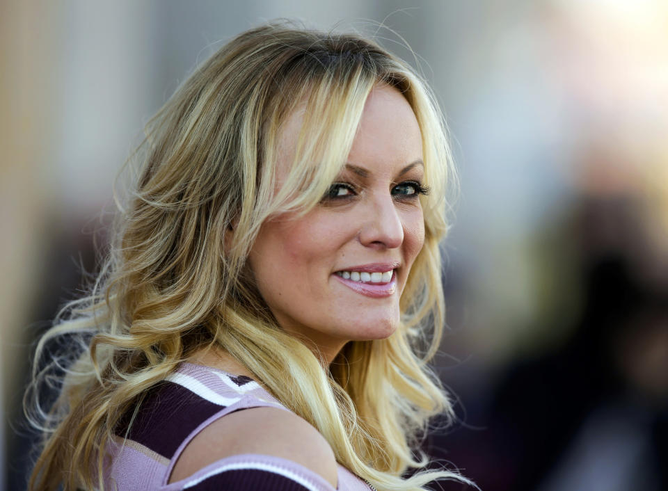 """FILE - In this Oct. 11, 2018, file photo, adult film actress Stormy Daniels attends the opening of the adult entertainment fair """"Venus,"""" in Berlin. When Donald Trump left the White House in January 2021, he remained """"Individual-1"""" in the federal campaign finance crimes case against his former attorney, Michael Cohen. The prosecution stemmed from six-figure payments Cohen arranged to Daniels and former Playboy model Karen McDougal, to keep them quiet during the campaign about alleged affairs with Trump. (AP Photo/Markus Schreiber, File)"""
