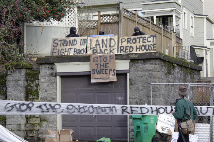 Masked protesters by an occupied home speak with a neighborhood resident opposed to their encampment and demonstration in Portland, Ore., on Wednesday, Dec. 9, 2020. Makeshift barricades erected by protesters are still up in Oregon's largest city a day after Portland police arrested about a dozen people in a clash over gentrification and the eviction of a family from a home. (AP Photo/Gillian Flaccus)