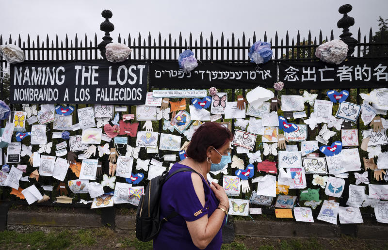 A woman passes a fence outside Brooklyn's Green-Wood Cemetery adorned with tributes to victims of COVID-19, Thursday, May 28, 2020, in New York. The memorial is part of the Naming the Lost project which attempts to humanize the victims who are often just listed as statistics. (AP Photo/Mark Lennihan)