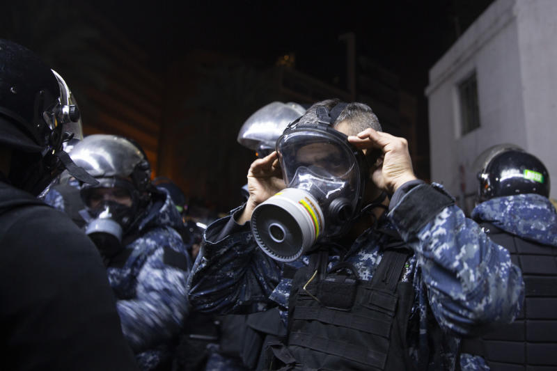 A Lebanese policeman adjusts his gas mask during clashes with supporters of Lebanon's former Prime Minister Saad Hariri, who burned tires and closed a road in Beirut, Lebanon, Friday, Dec. 20, 2019. (AP Photo/Maya Alleruzzo)