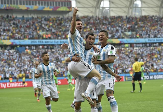 Argentina's Lionel Messi, left, is carried by his teammates Argentina's Angel di Maria (7) and Argentina's Marcos Rojo after scoring his side's first goal during the group F World Cup soccer match between Nigeria and Argentina at the Estadio Beira-Rio in Porto Alegre, Brazil, Wednesday, June 25, 2014. (AP Photo/Martin Meissner)