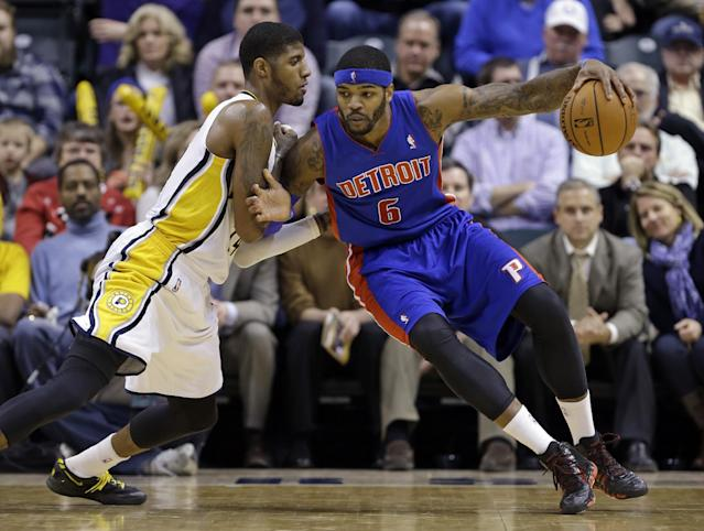 Indiana Pacers forward Paul George, left, defends Detroit Pistons forward Josh Smith in the second half of an NBA basketball game in Indianapolis, Monday, Dec. 16, 2013. The Pistons defeated the Pacers 101-96. (AP Photo/Michael Conroy)