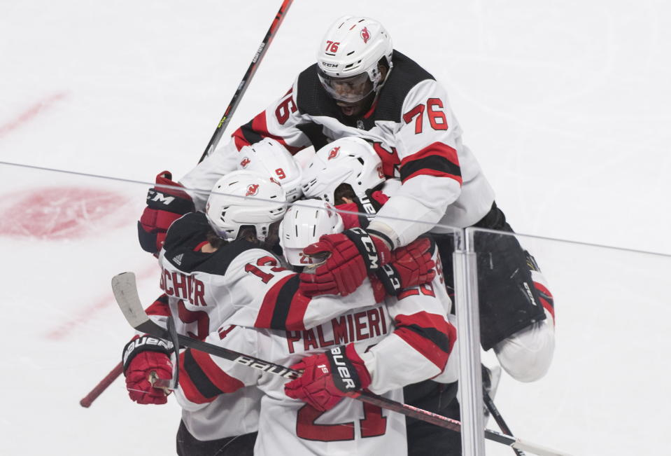 New Jersey Devils' Kyle Palmieri (21) celebrates with teammates Taylor Hall (9), Nico Hischier (13) Damon Severson (28) and P.K. Subban (76) after scoring against the Montreal Canadiens during overtime in an NHL hockey game in Montreal, Saturday, Nov. 16, 2019. (Graham Hughes/The Canadian Press via AP)