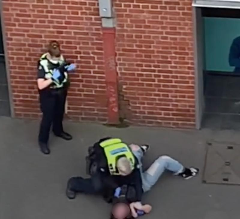 Photo shows a police officer pressing a woman into the ground.