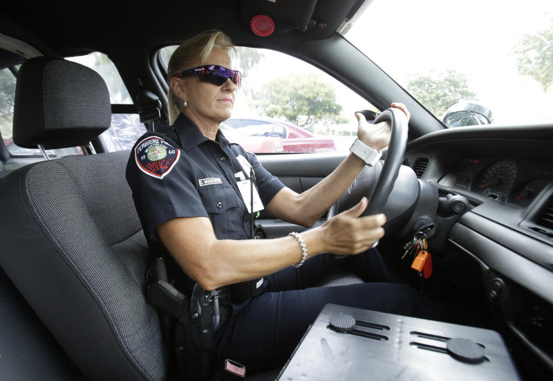 In this photo taken Thursday, Aug. 22, 2013, Dara Van Antwerp, the school resource officer at Panther Run Elementary School, drives her patrol car in Pembroke Pines, Fla., in the suburbs of Fort Lauderdale. The armed school resource officer who will be permanently stationed on campus, though crime in this middle class community has been on a steady decline. The decision comes in the wake of the Sandy Hook Elementary School shootings in Newtown, Conn., last year. (AP Photo/Wilfredo Lee)