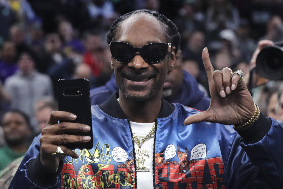 Rapper Snoop Dogg gestures to fans prior to the first half of an NBA basketball game between the Boston Celtics and Los Angeles Lakers in Boston, Monday, Jan. 20, 2020. (AP Photo/Charles Krupa)