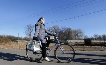A member of an election commission carries a mobile election box as she cycles to collect votes from local residents during a parliamentary election, in Horodyshche near Chernihiv, October 26, 2014. REUTERS/Stringer