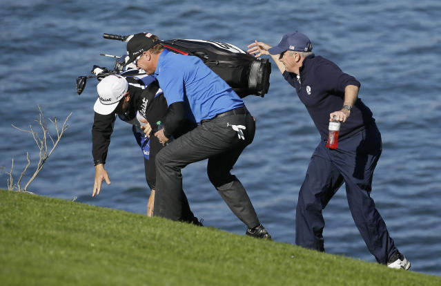 Jay Monahan, right, and Charley Hoffman, center, try to keep Hoffman's caddie from falling while climbing up the sixth fairway of the Pebble Beach Golf Links during the third round of the AT&T Pebble Beach Pro-Am golf tournament, Saturday, Feb. 9, 2019, in Pebble Beach, Calif. (AP Photo/Eric Risberg)