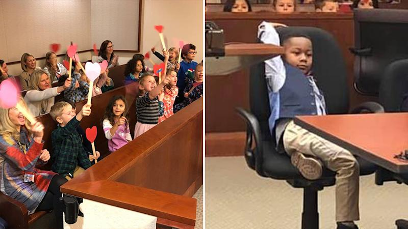 Michael Orlando Clark Jr sits in the court room on the right while his classmates, waving hearts on wooden sticks, support him (left).