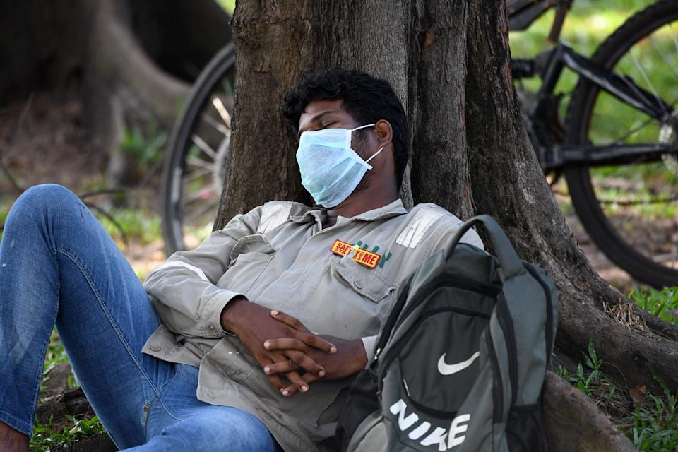 """A man wearing a face mask, as a preventive measure against the spread of the COVID-19 coronavirus, and a tag that reads """"Safety starts with me,