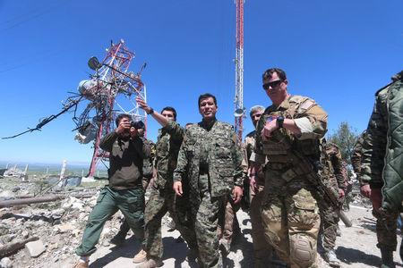A U.S. military commander walks with a commander from the Kurdish People's Protection Units (YPG) as they inspect the damage at YPG headquarters after it was hit by Turkish airstrikes in Mount Karachok near Malikiya, Syria