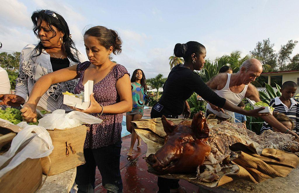 <p>Carmen Gonzalez (back C) approaches the roast pig being served at her quinceanera (coming-out for 15-year-olds) party in Havana.</p>