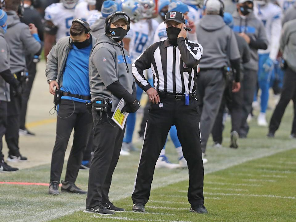 Detroit Lions interim head coach Darrell Bevell watches a replay with an official during the second half against the Chicago Bears at Soldier Field, Dec. 6, 2020.