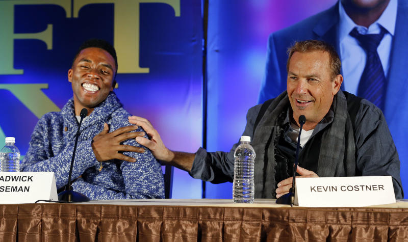 """Actors Chadwick Boseman, left, and Kevin Costner appear at a news conference for the movie """"Draft Day"""" in New York on Friday, Jan. 31, 2014, two days before the NFL football Super Bowl in East Rutherford, N.J. (AP Photo/Paul Sancya)"""