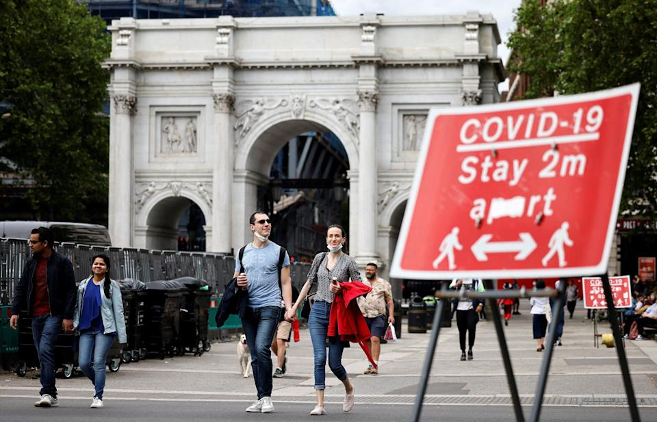 Pedestrians walk past a sign asking people to social distance, near Marble Arch in central London (Photo: TOLGA AKMEN via Getty Images)