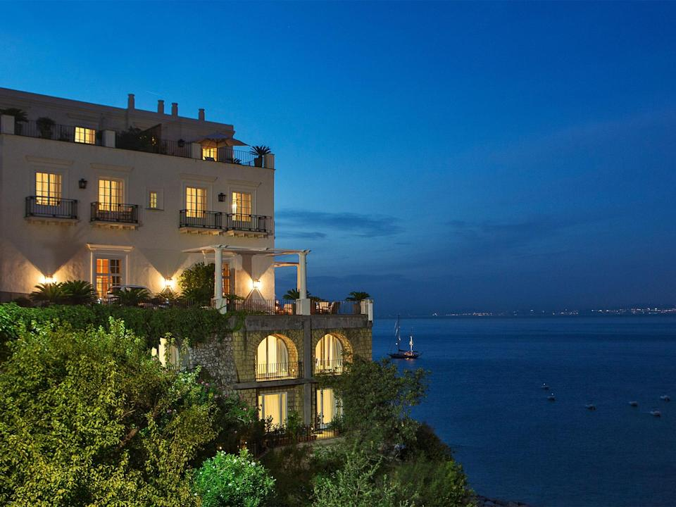 """The J.K. Place Capri is the Italian townhouse hotel, redefined. The attention to detail here is painstaking, from the discreetly attentive service to a stylish marine color scheme that might have appeared on a 1930s racing yacht. This nautical theme is appropriate for a hotel that rises like the upper decks of a liner above the Mediterranean, with views across to Sorrento, <a href=""""https://www.cntraveler.com/story/how-to-spend-24-hours-in-naples-according-to-a-local?mbid=synd_yahoo_rss"""" rel=""""nofollow noopener"""" target=""""_blank"""" data-ylk=""""slk:Naples"""" class=""""link rapid-noclick-resp"""">Naples</a>, and Vesuvius. Capri town is just 10 minutes away on the hotel's shuttle, but you'd be surprised at just how many guests never take up the offer. The satisfyingly large swimming pool is difficult to tear yourself away from, and as evening approaches, signature cocktails such as the JK Spritz (a gingery variation on the Venetian classic) have a way of appearing, accompanied by inventive nibbles that ease guests into dinner on the restaurant terrace. But there's also a strong focus on food: Neapolitan chef Eduardo Estatico's menu is light, seasonal, and also playful—don't miss his Cucciolone, a popsicle variant on the classic pastiera pie of Estatico's home town. If the Italian <em>dolce vita</em> is all about living the good life with class, style, and confidence, J.K. Place Capri must be the cult's high temple."""