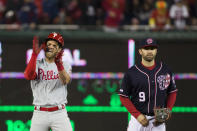 Philadelphia Phillies' Bryce Harper, left, celebrates his RBI hit while on second base with Washington Nationals second baseman Brian Dozier during the sixth inning of a baseball game at Nationals Park, Tuesday, April 2, 2019, in Washington. (AP Photo/Alex Brandon)