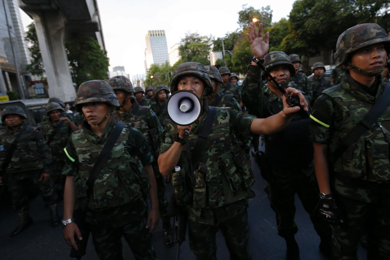 Soldiers try to control the crowd during a protests against military rule in central Bangkok, a day after Thai army chief seized power in a coup May 23, 2014. Several hundred people including students gathered in a central shopping district despite a ban on protests by five or more people to voice their opposition to military rule. REUTERS/Damir Sagolj (THAILAND - Tags: SOCIETY CIVIL UNREST)