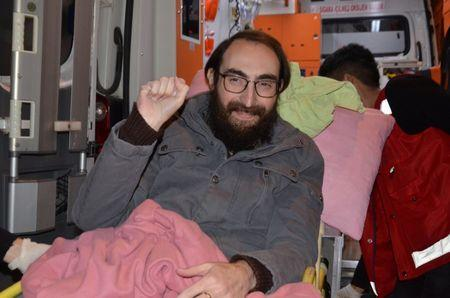 Semih Ozakca, a 28-year-old Turkish teacher who has been on hunger strike for months to protest about losing his job in the government's purge since a failed coup attempt last year and released from jail pending his trial on terrorism-related charges, gestures as he leaves an ambulance upon his arrival at his home in Ankara, Turkey, October 20, 2017. Picture taken October 20, 2017. Depo Photos via REUTERS