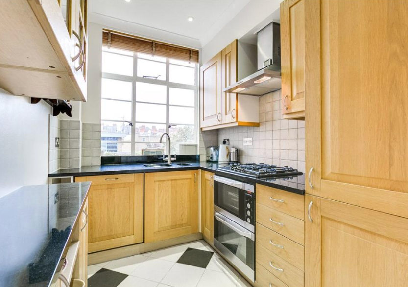 The kitchen features traditional furniture with black and white tiled flooring (Right Move)