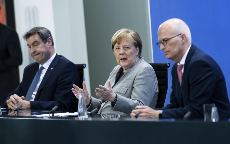 Markus Soder, Prime Minister of Bavaria, left, Germany's Chancellor Angela Merkel, center, and Peter Tschentscher, First Mayor of Hamburg, speak at a press conference in the Federal Chancellery, Berlin, Wednesday April 15, 2020. After much-anticipated talks Wednesday with Germany's 16 state governors, Chancellor Angela Merkel set out a plan for the first steps of a cautious restart of public life — following countries including neighboring Austria and Denmark in launching a slow loosening of restrictions. (Bernd von Jutrczenka/Pool via AP)